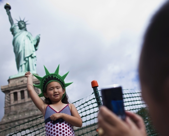 A girl poses for her father as they visit the Statue of Liberty and Liberty Island during its reopening to the pu