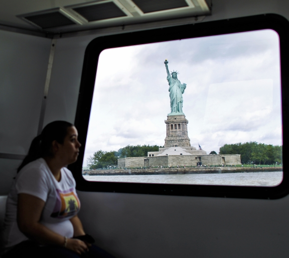 A woman rides a ferry to visit the Statue of Liberty and Liberty Island