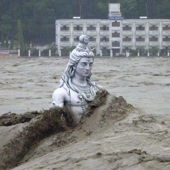 The statue of a Lord Shiva is submerged by flood waters of the river Ganges in Uttarakhand