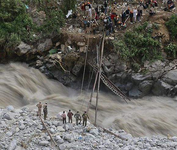 Soldiers work to install a temporary footbridge over a river to rescue the stranded