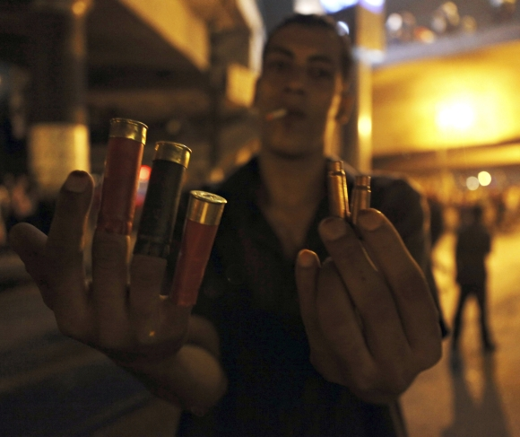 An anti-Morsi protester shows spent shell casings and rubber bullets during clashes with members of the Muslim Brotherhood and supporters of ousted the Egyptian president near Tahrir Square