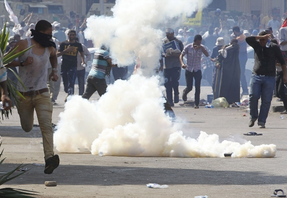 Protesters who support Morsi react to tear gas fired by riot police during clashes outside the Republican Guard building in Cairo