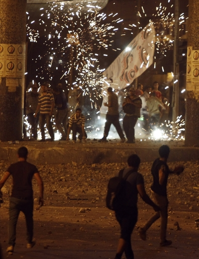 Flares are seen as members of the Muslim Brotherhood and supporters of Morsi clash with anti-Morsi protesters near Maspero