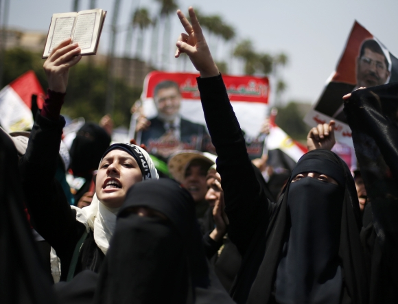 A protester, who supports former Egyptian President Mohamed Mursi, holds up a copy of the Koran as she and others march near Cairo University after Friday prayers in Cairo