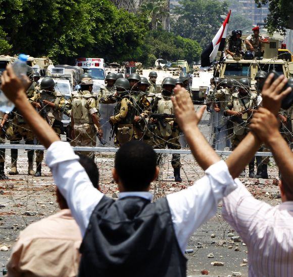 Members of the Muslim Brotherhood shout slogans in front of army soldiers at Republican Guard headquarters in Nasr City, on Monday.