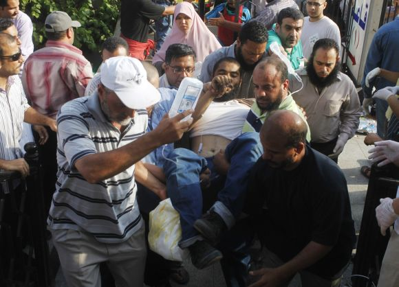 Supporters of Mohamed Mursi help a wounded supporter outside the Republican Guard headquarters in Cairo.