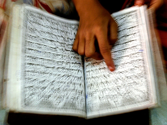 A Muslim girl reads the Koran inside a Madrasa in Mumbai