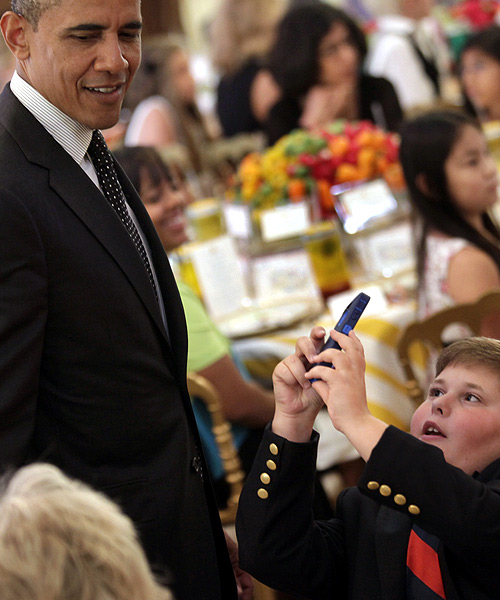 A boy takes pictures of US President Barack Obama at the second annual 'kids' state dinner', to honor the winners of a nationwide recipe challenge to promote healthy lunches, at the White House in Washington