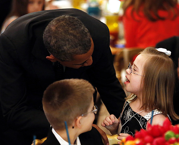 Obama talks with Makenna Hurd of Mascot during the kids' state dinner held in the East Room of the White House
