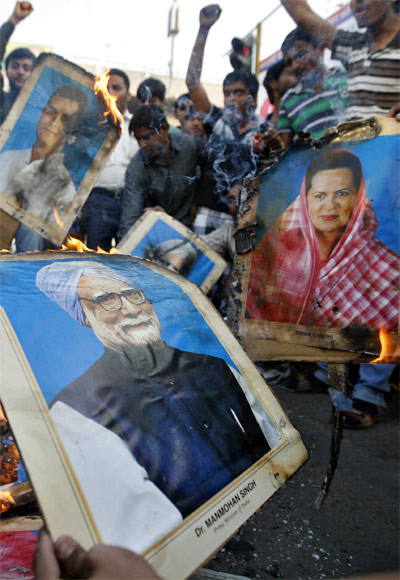 Demonstrators burn portraits of Prime Minister Manmohan Singh, Congress President Sonia Gandhi and vice president Rahul Gandhi