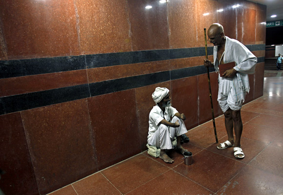 A man dressed like Mahatma Gandhi talks to a beggar while walking through a Delhi subway
