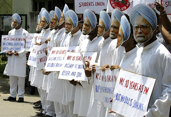 -Demonstrators wearing masks of India's Prime Minister Manmohan Singh hold placards during a protest