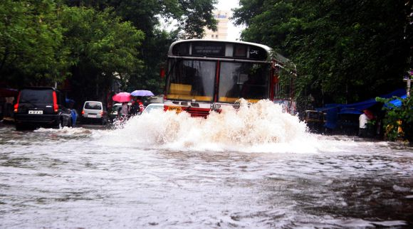 A bus wades through a waterlogged road in Thane on Friday