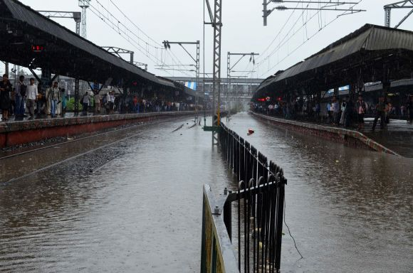 Commuters wait for trains as rain water inundates tracks at Thane station on Friday