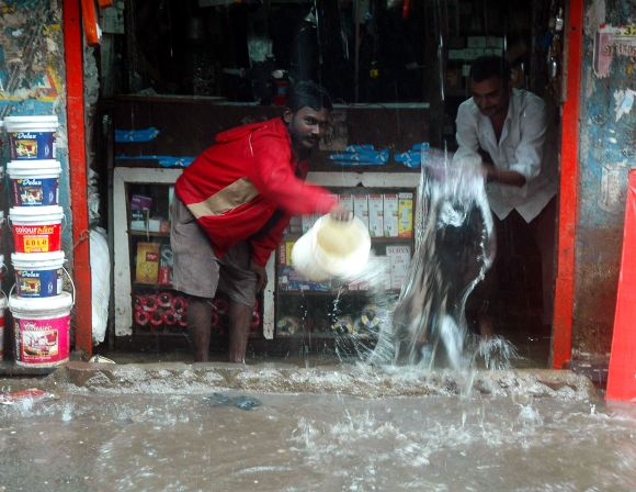 Shopkeers pour out buckets of rain water that entered a store in Sion on Friday