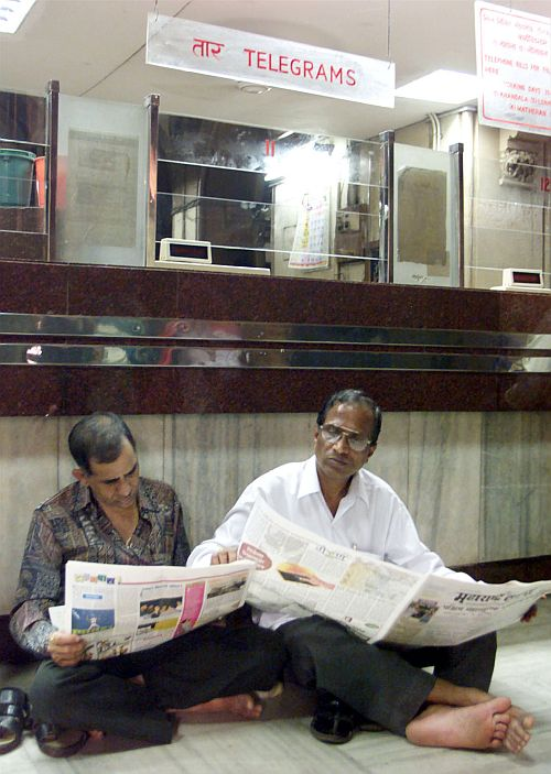 Telecom workers read newspapers in front of their counters in Mumbai