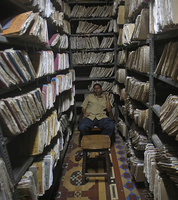 An employee sleeps in the record section room of the Central Telegraph Office in Mumbai