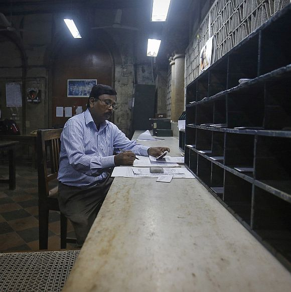 An employee writes down addresses before dispatching telegrams inside the delivery section room of the Central Telegraph Office in Mumbai