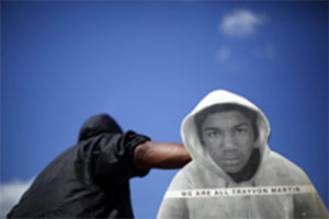 A man holding a cardboard cut out of Trayvon Martin protests the acquittal of George Zimmerman.