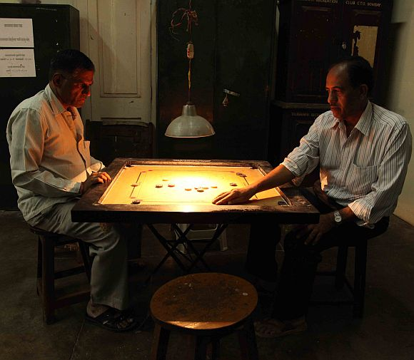 Two operators playing carrom at a telegraph office