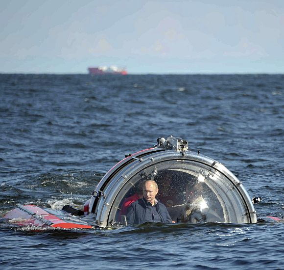Russia's President Vladimir Putin is seen through the glass of C-Explorer 5 submersible after a dive to see the remains of the naval frigate Oleg, which sank in the 19th century, in the Gulf of Finland in the Baltic Sea July 15