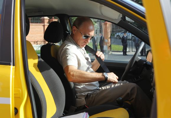 Russia's Prime Minister Vladimir Putin fastens his seat belt as he prepares to drive a  Russian-made Lada Kalina car in the city of Khabarovsk.