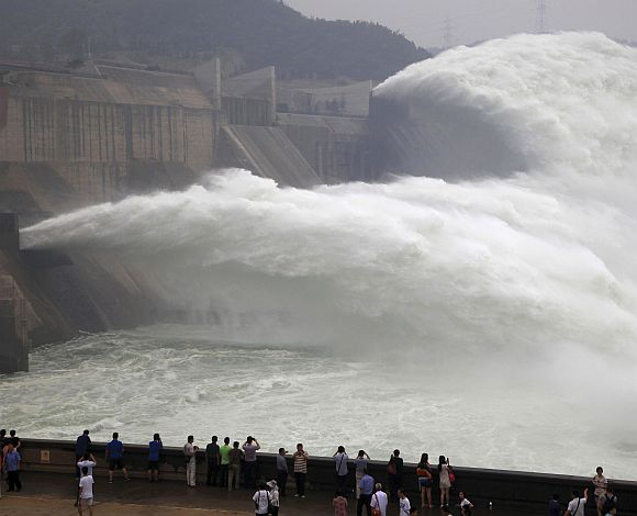 Visitors watch water gushing from the section of the Xiaolangdi Reservoir on the Yellow River