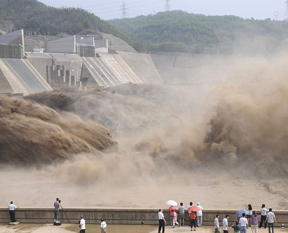 Visitors look at water gushing from the section of the Xiaolangdi Reservoir on the Yellow River