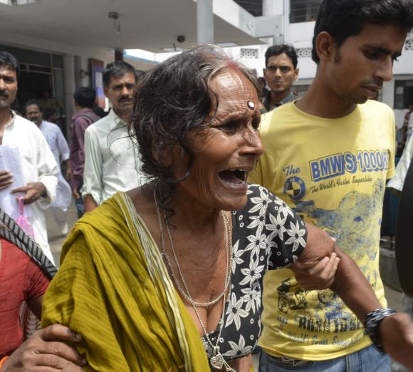 A woman cries after her grandson, who consumed a meal at school on Tuesday, died at a hospital in Patna