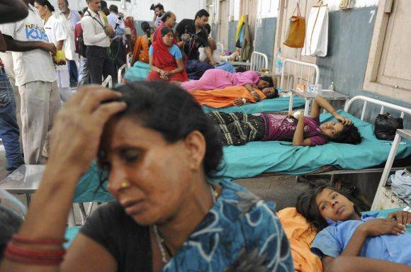 Asha Devi sits next to her sick daughter Savita, at a hospital in Patna