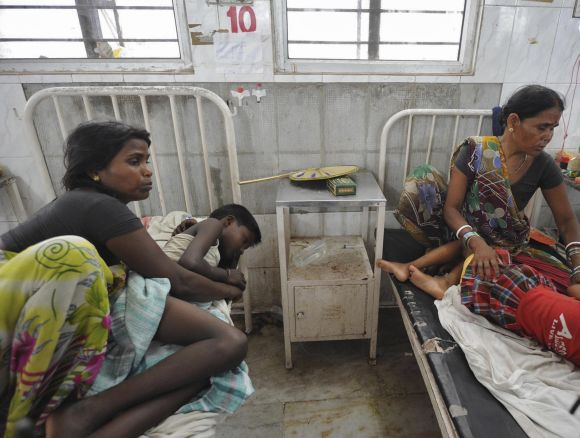 Women sit next to their children, who were hospitalised after consuming the meal at school
