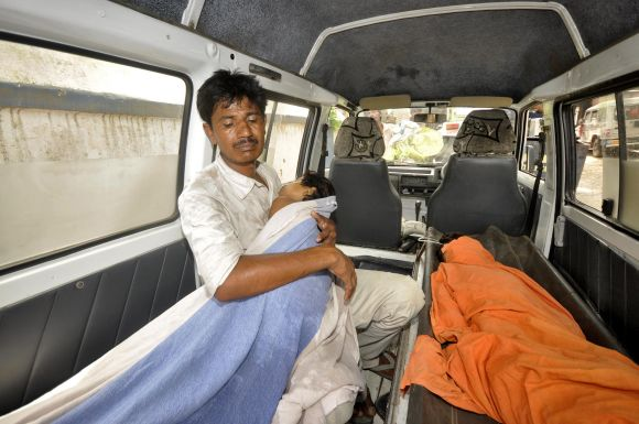 A man holds his sick child on thier way to the hospital in Patna