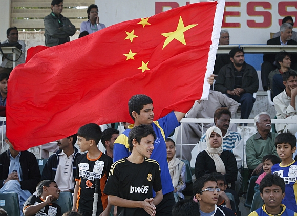 Pakistani boy waves a national flag of China in Karachi