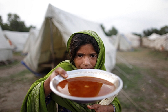 A girl holds up her evening meal at an assistance centre for flood victims in Nowshera in Pakistan's northwest Khyber-Pakhtunkhwa Province