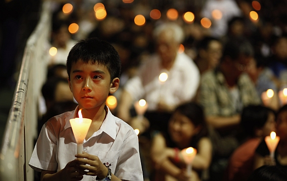 A boy, accompanied by his parent, participates in a candlelight vigil at Hong Kong's Victoria Park to mourn those who died in a military crackdown on pro-democracy movement at Beijing's Tiananmen Square in 1989