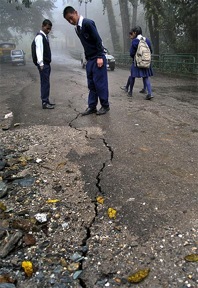 Schoolboys stop to look at a crack running down a road following an earthquake in Gangtok