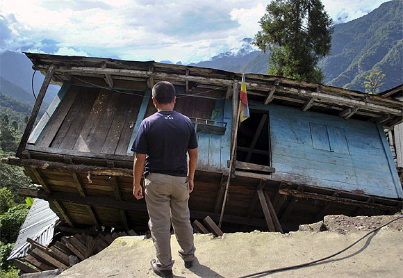 A man stands in front of his house, which was damaged by an earthquake