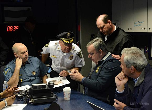Federal, state and local officials strategise in mobile state police command post