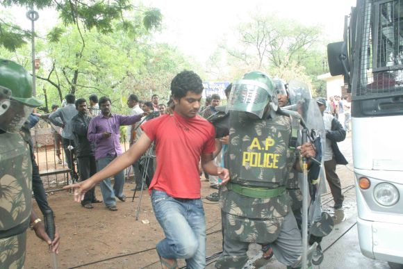 A security personnel detains a Telangana supporter during clashes