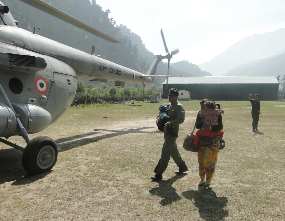 An IAF trooper helps a lady and child into a helicopter.