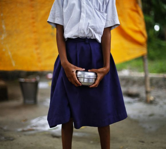 A school girl holds a container to receive her free mid-day meal at Brahimpur village in Bihar's Chapra district.