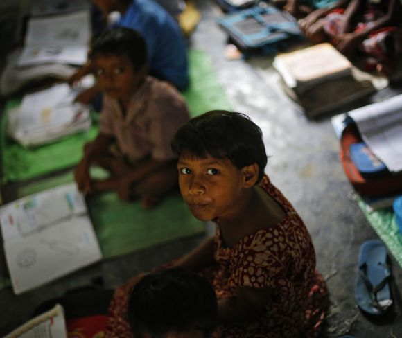 A school girl watches the camera while studying inside her classroom before having the free mid-day meal in Bihar