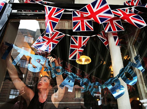 Hayley Simmonds, an employee at the British restaurant and grocery Tea & Sympathy, hangs a sign in the window celebrating the birth of Catherine, Duchess of Cambridge, and her husband Prince William's first child