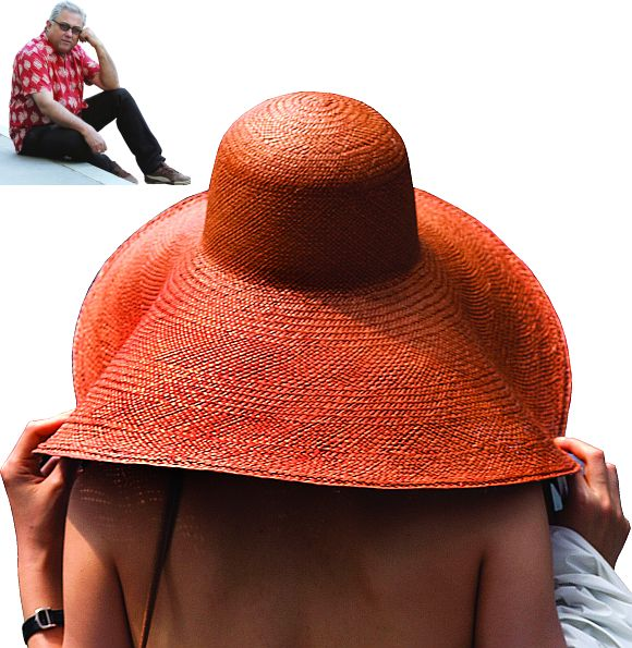 A woman covers herself with a large hat in Times Square during a heat wave in New York. (Inset) Aseem Chhabra