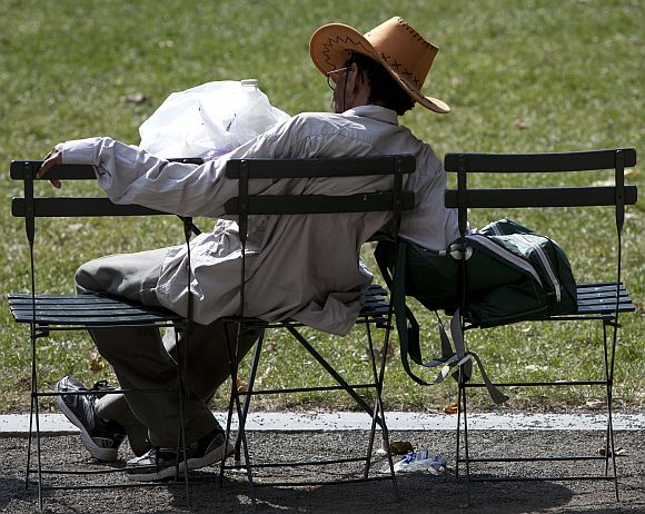 A man sleeps on chairs in Bryant Park during a heat wave in New York