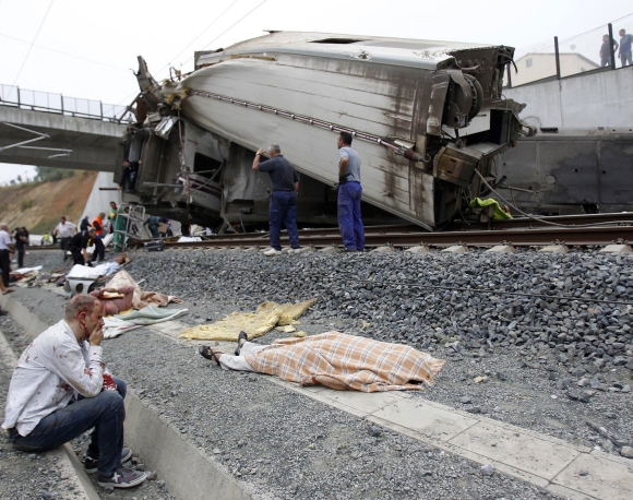 A wounded victim sits near the train crashed site