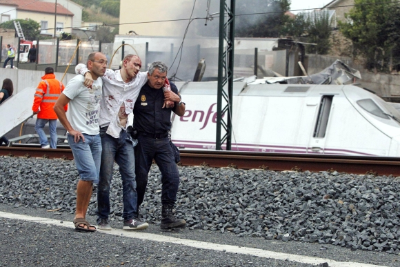 Rescue workers help a victim of a train crash near Santiago de Compostela