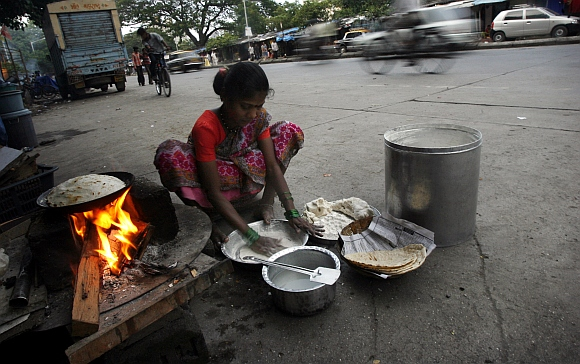 A woman cooks food on a street in front of her shanty in Mumbai