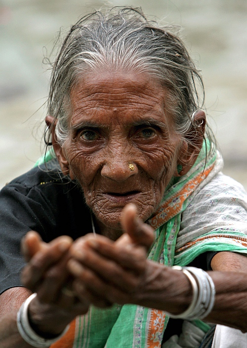 An elderly homeless woman begs on a street in New Delhi