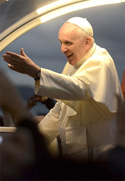 Pope Francis greets faithful as he is driven along the beachfront in the Copacabana neighborhood of Rio de Janeiro